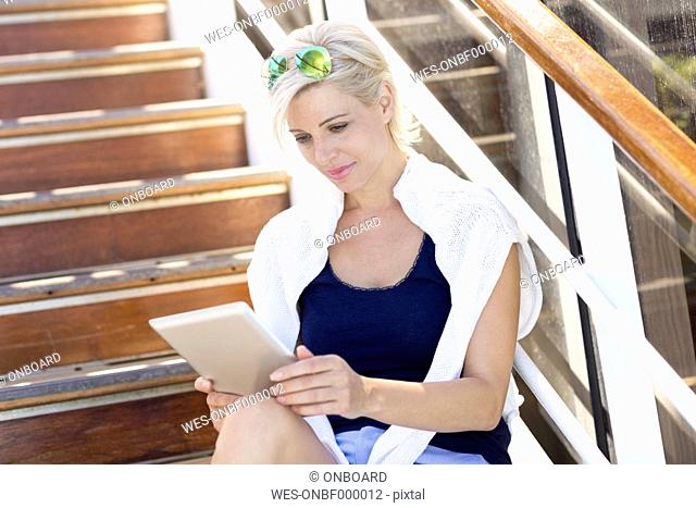 Mature woman with tablet sitting on a stairway, cruise ship