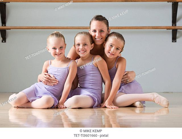 Portrait of female instructor with ballet dancers 6-7 in dance studio