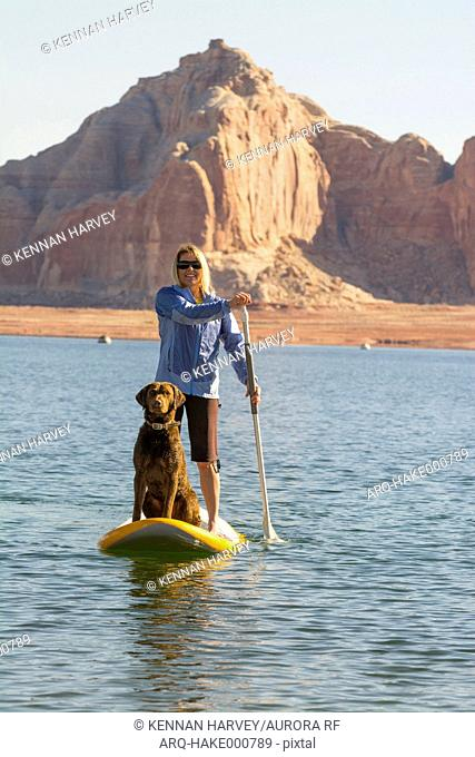 A woman and her dog paddleboarding on Lake Powell, Wahweap Marina, Glen Caynon National Recreation Area, Page, Arizona