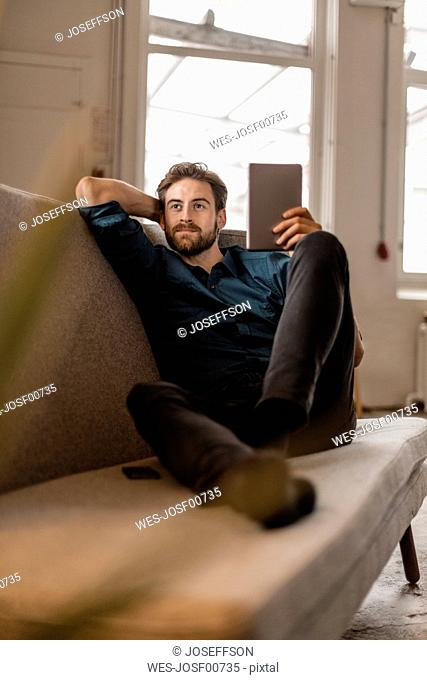 Portrait of young freelancer sitting on the couch with tablet