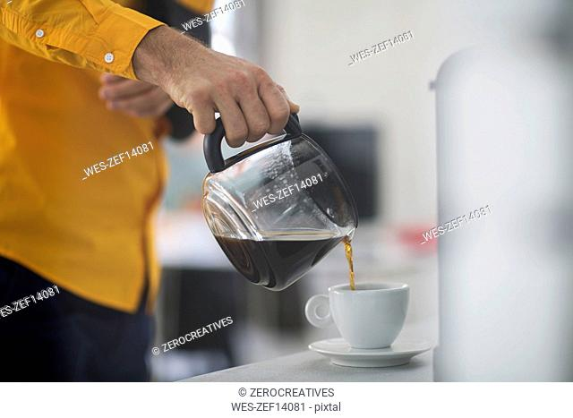 Employee with sling pouring coffee into cup at work