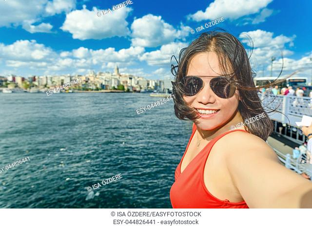 Beautiful Chinese woman takes selfie with view of Galata Tower on background in Istanbul,Turkey
