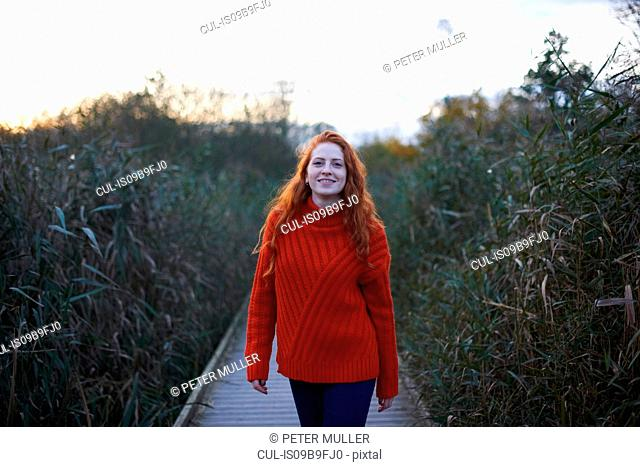 Portrait of young woman walking along rural pathway