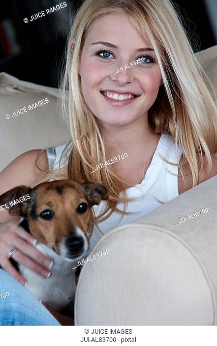 Young woman smiling with dog on sofa