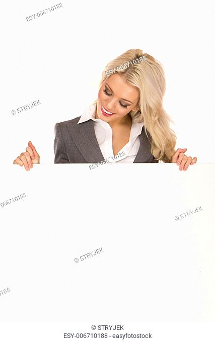 Portrait of a beautiful sexy blonde happy business woman holding a blank billboard. Ready to add text
