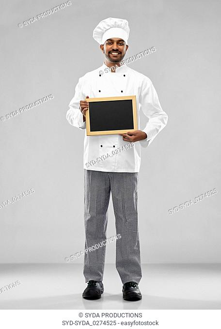 happy male indian chef in toque with chalkboard