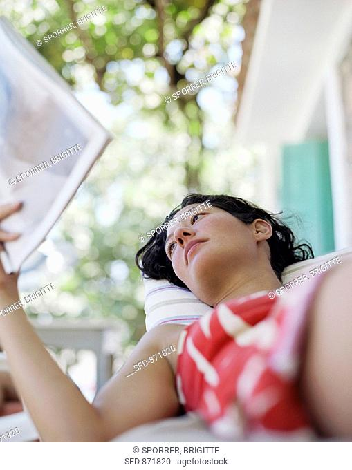 Young woman lying on a terrace and reading a magazine