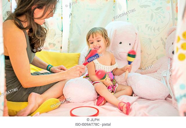 Mother and daughter sitting in play tent, playing with musical instruments