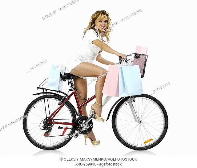 Beautiful young woman with many colorful bags after shopping on a bicycle Fashion leisure and healthy lifestyle concept Isolated silhouette on white background