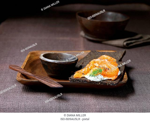 Pumpernickel with cream cheese, smoked salmon with cracked black pepper on wooden plate