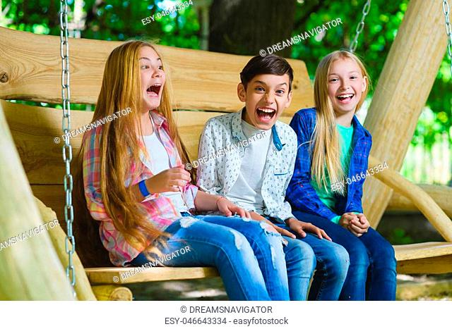 Smiling girls and boy having fun at playground. Children playing outdoors in summer. Teenagers on a swing