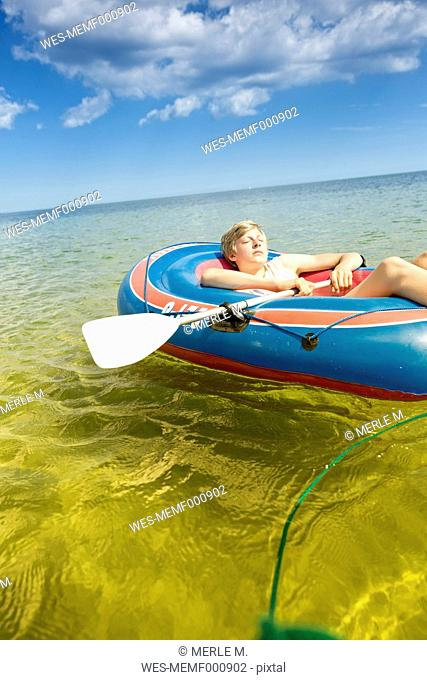Germany, Niendorf, young boy relaxing in an inflatable boat