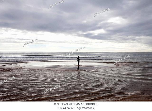 Person on small island during flood tide at Rauðasandur, Westfjords, Iceland