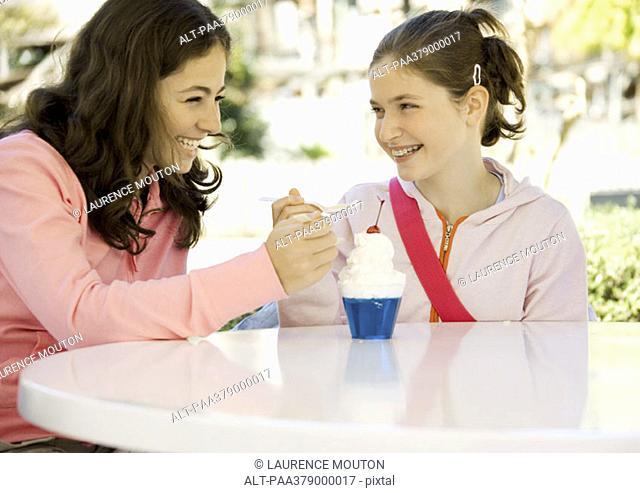 Two preteen girls sharing dessert