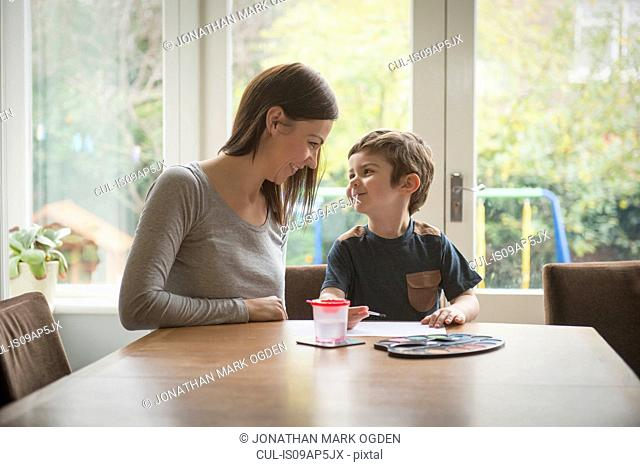 Boy smiling at mother as he paints on paper at table in living room