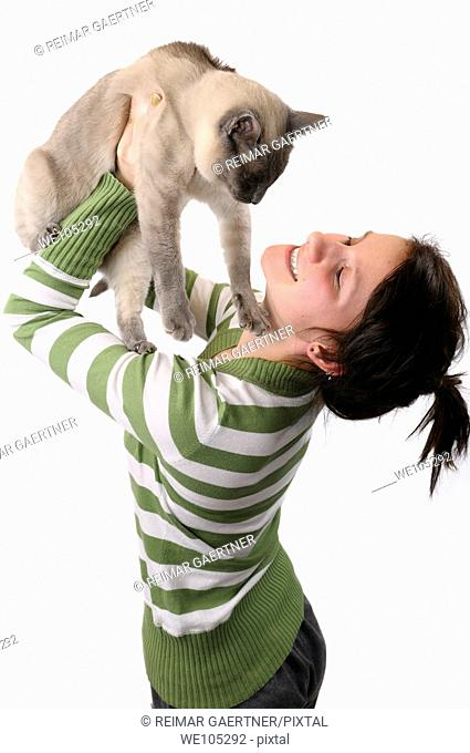 Smiling young girl lifting a Siamese cat to her face on a white background