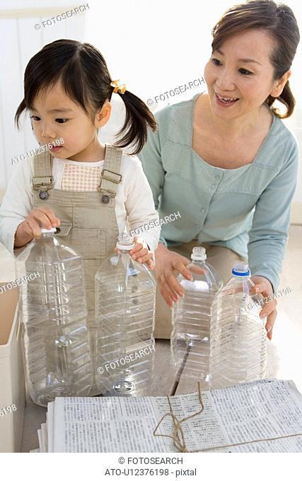 Girl and Grandmother Recycling Plastic Bottles and Waste Newspaper