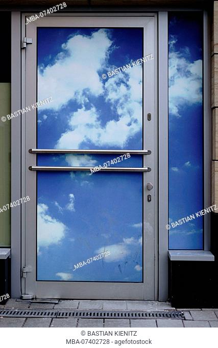 An entrance door with a blue sky and clouds