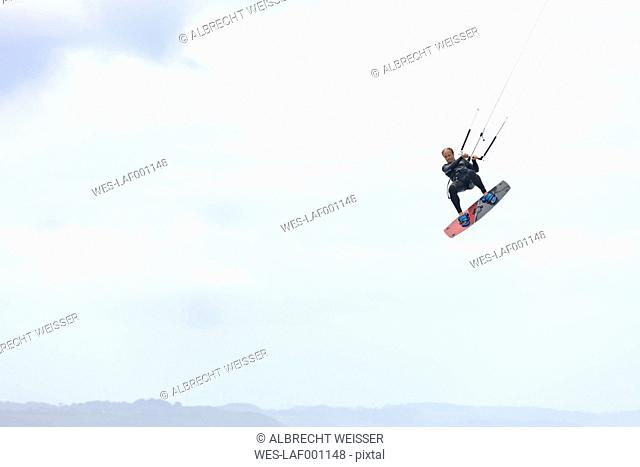 France, Bretagne, Finistere, man up in the air with his kiteboard