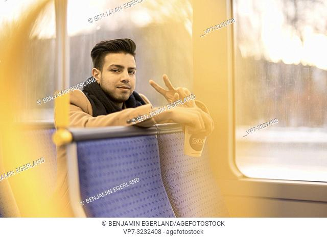 young man sitting in public transport, holding plastic cup, in Munich, Germany