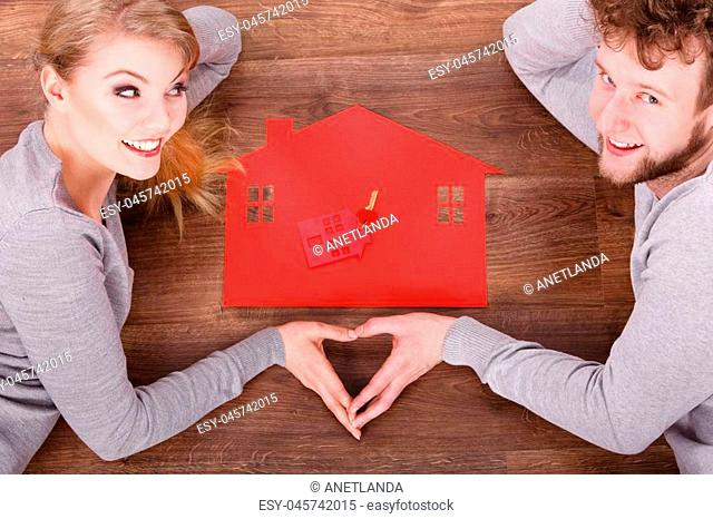 Love romance relationship home security safety concept. Couple with family symbols. Girl and boy forming heart with hands on house and keys