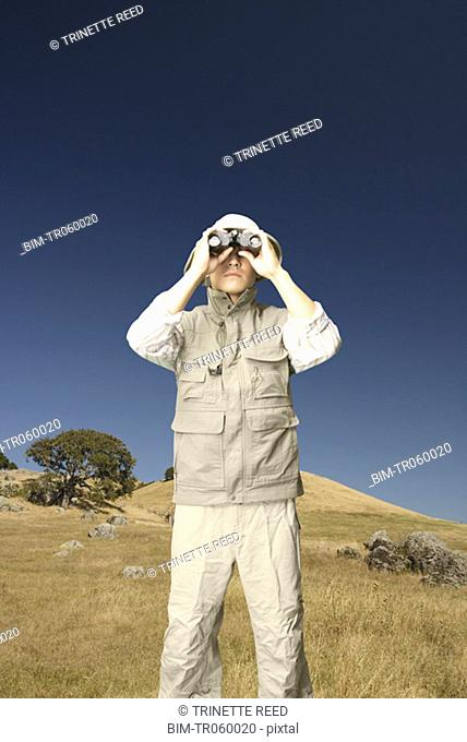 Explorer using binoculars in grassy area