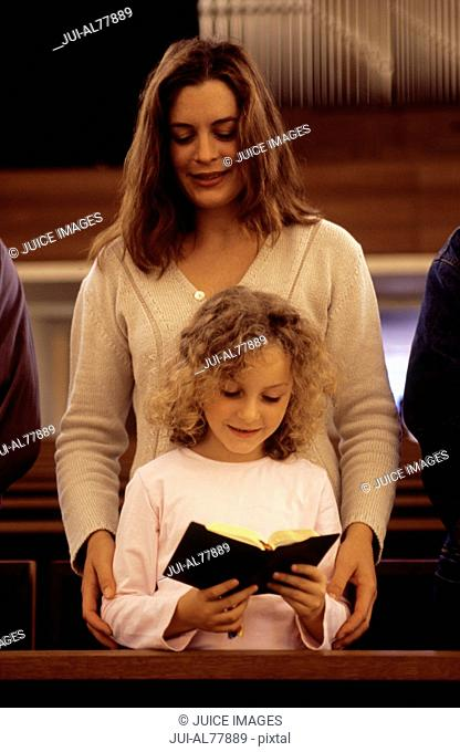 Woman and child reading a Bible in church