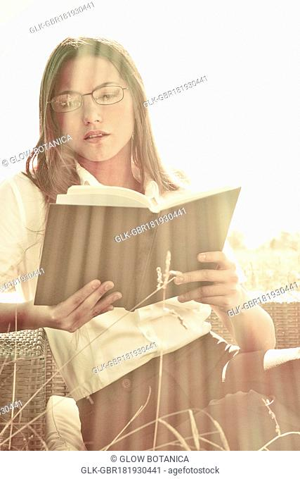 Businesswoman reading a book on a sofa