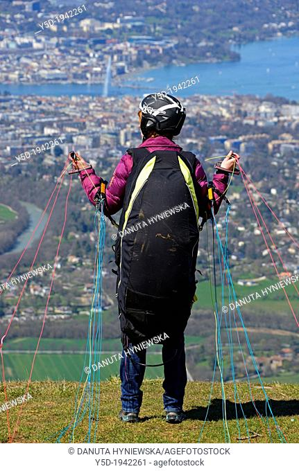 woman waiting for wind, ready for taking off the paraglider from Mont Saleve in France, panorama of Geneva and Geneva Lake in Switzerland below