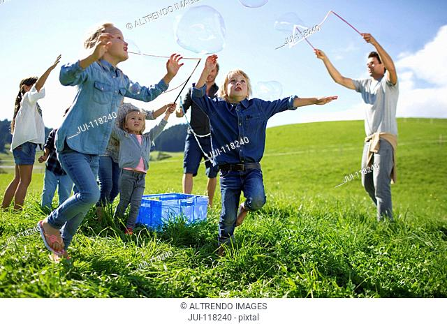 Fathers And Children Making Giant Bubbles In Countryside