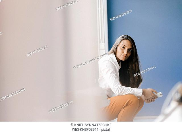 Young businesswoman sitting at window, using smartphone
