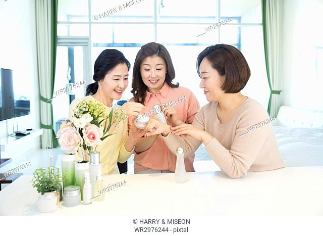 Portrait of three middle aged women sharing cosmetic