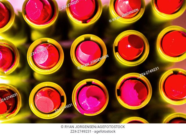 Still life fashion photo on a patterning of bright and colourful lipstick makeup positioned in symmetric form