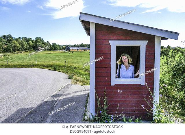 JÄRNA, SWEDEN Saltå Kvarn. Saltå mill and surrounding rural area with fields ecological food store. Portrait of woman at busstop