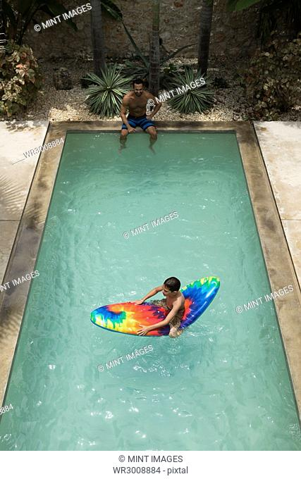 High angle shot of a boy sitting on a pool raft, watched by a man at the edge of swimming pool