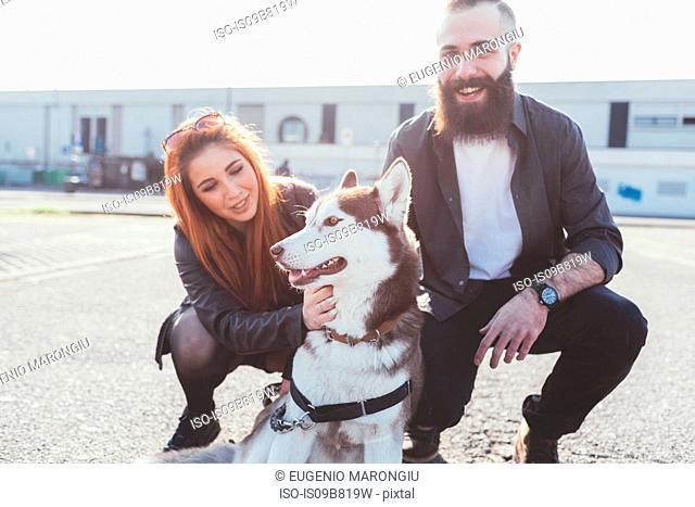 Couple stroking dog smiling