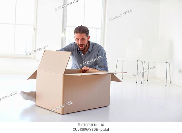 Young man sitting on floor opening cardboard box in new house