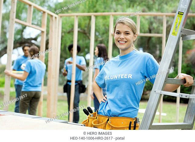 Portrait of confident woman by ladder with volunteers building wooden frame in background