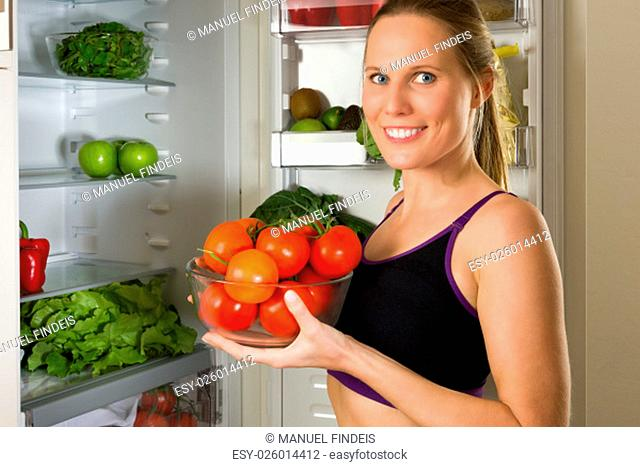 Sporty, Caucasian woman showing vegetables for healthy eating in front of a refrigerator