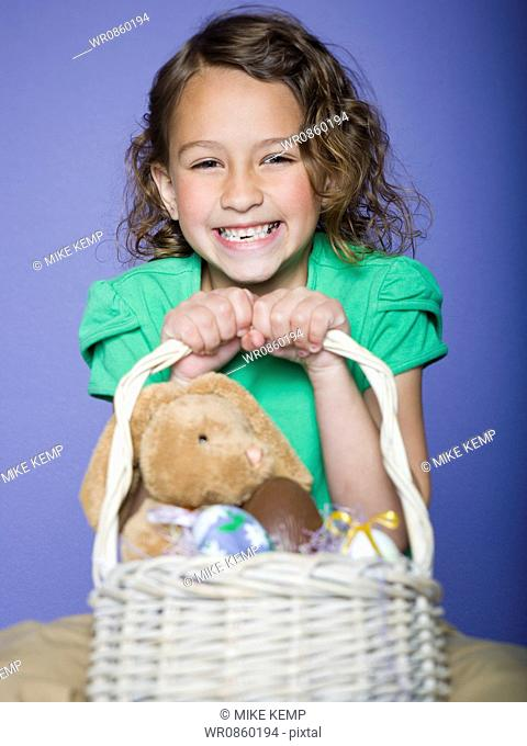 Portrait of a girl holding Easter eggs in a wicker basket