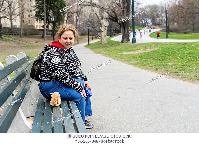 New York City, USA. Female, caucasian dogwalker, walking the dog of one of her customer's through Central Park, Manhattan