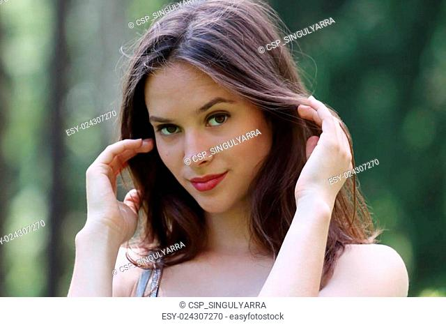 Close-up face of beautiful girl straightens her hair