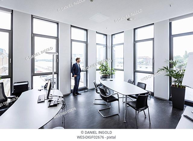 Businessman standing in his office looking out of the window