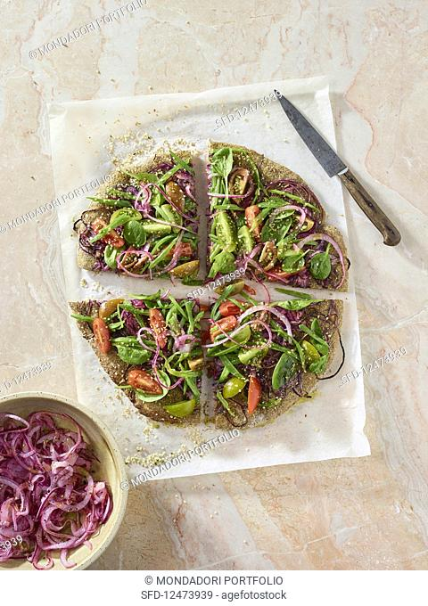 A hemp pizza with red onions and tomatoes