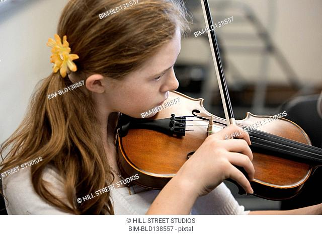 Caucasian girl playing the violin in music class