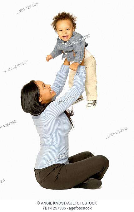 Attractive young mother sitting and holding up her smiling one year old son