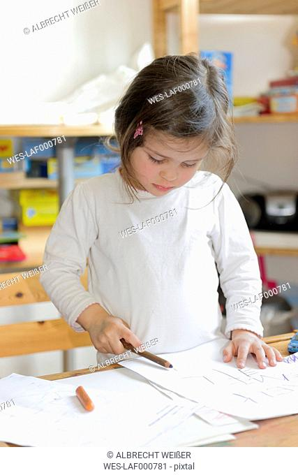 Girl at home writing on sheet of paper