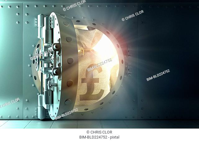 Back lit money bags with British pound symbol in vault