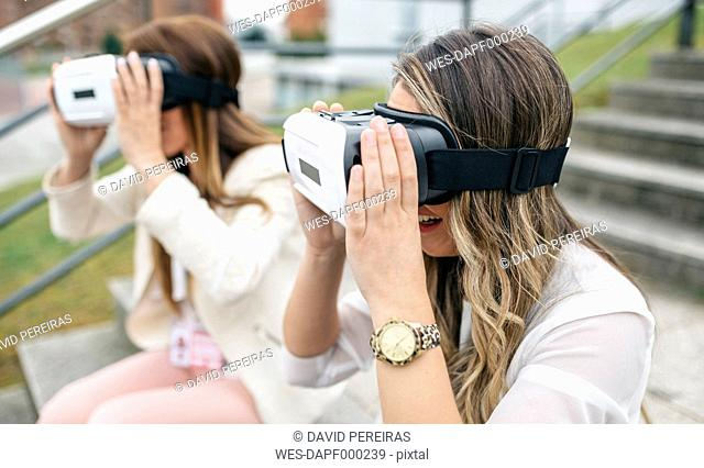 Two women having fun with VR glasses sitting outdoors