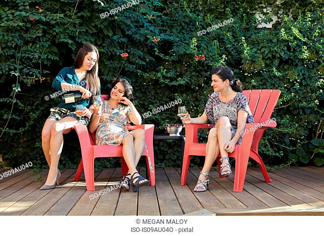 Three women drinking white wine on patio